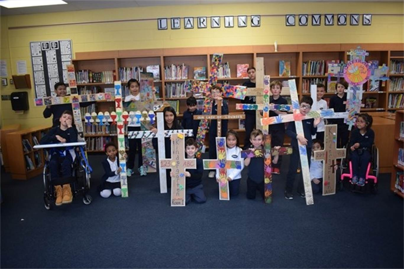 Our Lady of Lourdes students show off the 14 personalized crosses each class created to show their Catholic identity. Photo courtesy of Hamilton Mountain News.